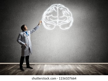 Conceptual image of young male doctor in white medical suit interracting with white glowing symbol of brains while standing inside empty room with gray wall on background.