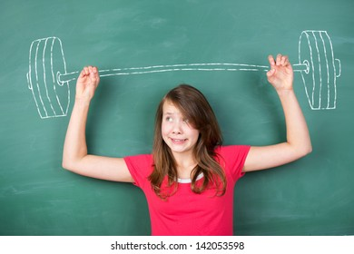 Conceptual image of a young schoolgirl trying to overcome a hard task by lifting a heavy barbell drawn in chalk in the green chalkboard