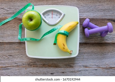 Conceptual images of healthy food lose weight and not make you fat, healthy, with green apples and banana roll with waist tape on the scale and dumbbell put on wood background with copy space.