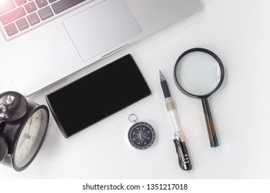 Conceptual images laptop, smartphone, alarm clock, compass, magnifying and pen on white background. Selective focus.