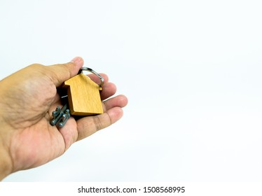 Conceptual isolated image of house keys hand-over after home financing. Hand holding keys attached to house-shape wooden key chain. Space for texts. Focus on key ring; other on gradient blur.