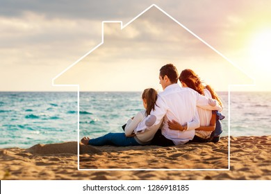 Conceptual late afternoon outdoor portrait of young parents sitting on beach with kids.Foursome giving back against sea and cloud background. House icon drawing around family.
