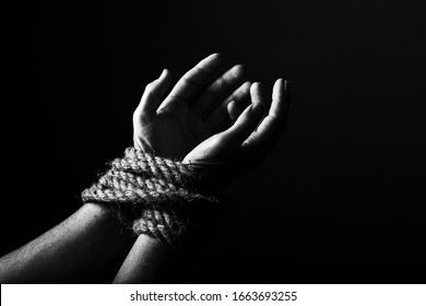 Conceptual monochrome image of woman hands tied with a coarse rope and selective lighting