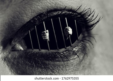 Conceptual monochrome photo of hands holding the bars of a prison inside a human eye