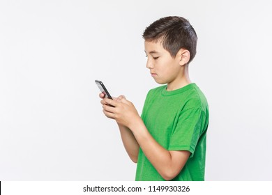 Conceptual photo of a boy texting on his cell phone in a studio setting.