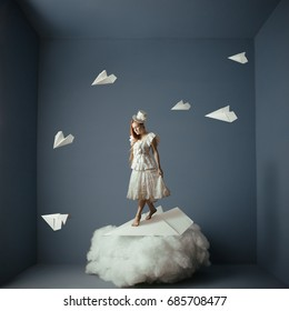 Conceptual photo manipulation of walk in the air. Girl and paper airplanes