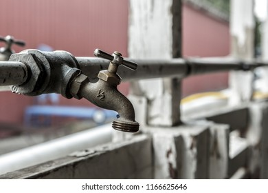 A conceptual photo of an old industrial water spigot and a pipe.
