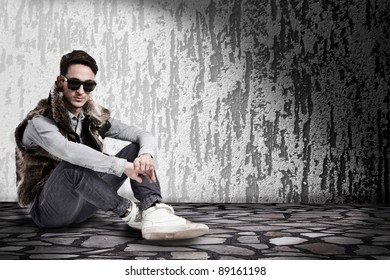 conceptual photo of young male sitting in a dark room wearing sunglasses