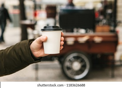 Conceptual photography. The person is holding a disposable glass in his hand with coffee or another hot drink. Street sale of hot drinks in the background.