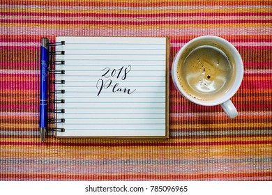 Conceptual plan - 2018 Plan words written on paper/notebook with a cup of coffee and pen on the table.