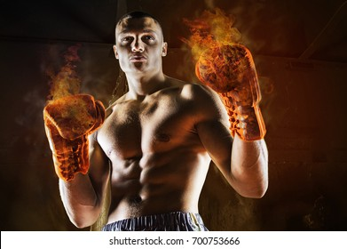 Conceptual Portrait of brutal boxer in fire sparks and smoke. Art Sport background.