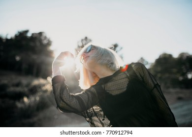 Conceptual portrait of cute blonde woman posing in profile with sunglasses and black clothes with sun backlighting in nature.