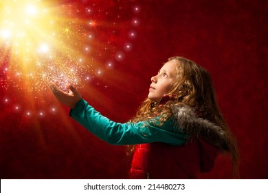 Conceptual portrait of cute young girl touching the stars against reddish galaxy background.