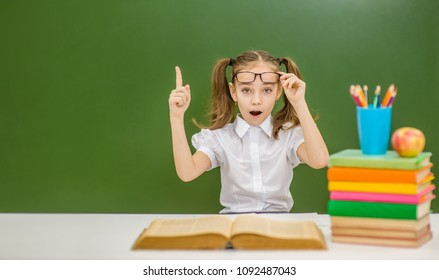 Conceptual portrait of  girl nerd student with surprising expression pointing up with finger against green background