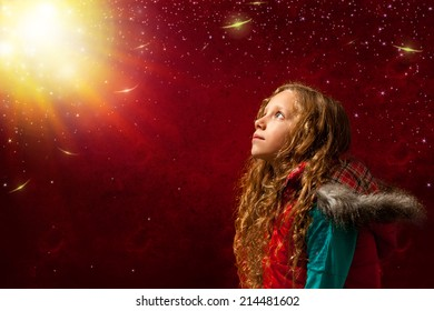 Conceptual portrait of girl staring at bright sun against reddish background.