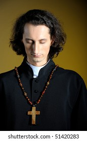 conceptual portrait of Praying priest with wooden cross . yellow background