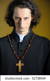 conceptual portrait of Praying priest with wooden cross praying. yellow background