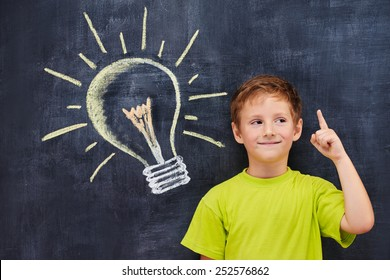 Conceptual portrait of redhead primary age school boy with pictured lightbulb