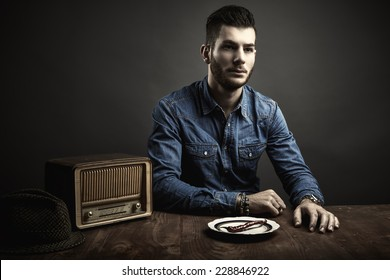 Conceptual portrait of young man sitting at a table, vintage style