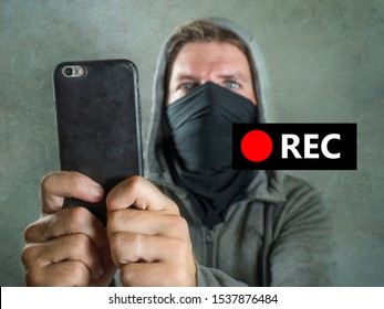 conceptual portrait of young rioter filming street chaos . ultra and radical man masked recording riot video on mobile phone during violent turmoil witnessing brutality at anti system demonstration