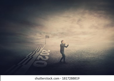 Conceptual scene of finishing the 2020 year, confident and determined businessman crosses the finish line and accomplish his mission and purpose. Winning a tough challenge, celebrating success at end.