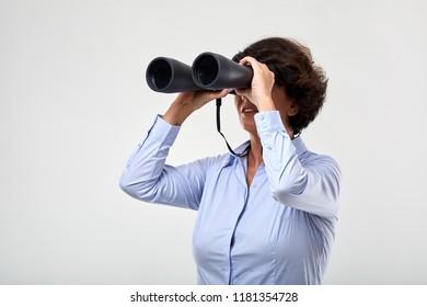 Conceptual shot of a mature businesswoman with big binoculars