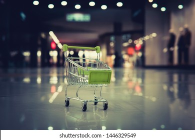 Conceptual shot of a small shopping cart put on the floor at blur background of shopping centre. Petty expenses in supermarket. Going for stuff in department store. Trolley as a symbol of purchasing