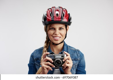 Conceptual shot of young female tourist traveling on bicycle with retro camera. Portrait of woman photographer in helmet.
