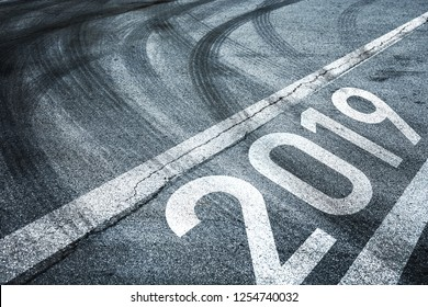 Conceptual start to the New Year. Number 2019 with abstract line mark on the asphalt road with tires tracks.