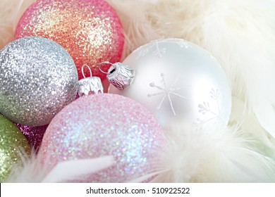 Conceptual still life close up of multiple color decorative glitter christmas festive bauballs together in white feathers, textured object, indoors. Xmas occasion shiny decorations, interior space.