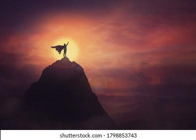 Conceptual sunset scene, superhero with cape standing brave on top of a mountain looks determined at horizon raising one hand up as a winning leader. Hero power and motivation, overcoming obstacles.