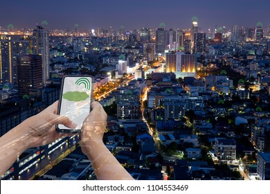 Conceptual tecnology communication hand holding cell phone signal with city building at night in double exposure