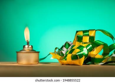Lampe à huile traditionnelle malaise conceptuelle appelée pelita avec ketupat décoratif pour la célébration de Hari Raya Aidilfitri