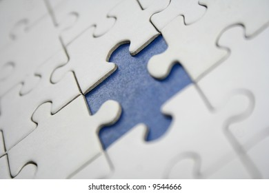 Conceptual white jigsaw puzzle with one blue missed piece