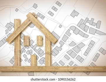Conceptual wooden house over an imaginary cadastral map of territory with buildings, fields and roads - concept image