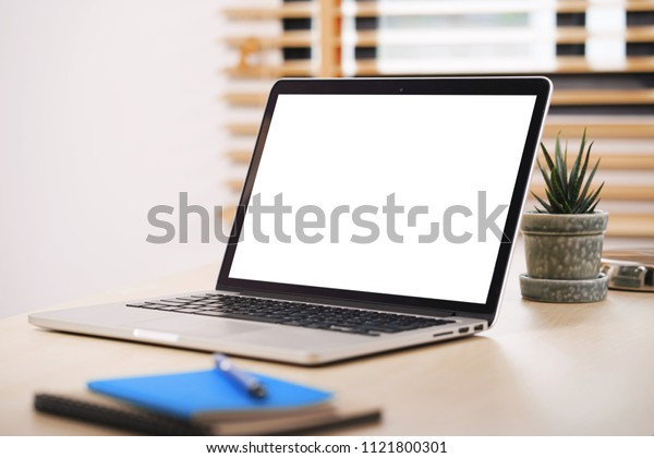 Conceptual workspace, Laptop computer with blank white screen on table.