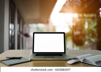 Conceptual workspace,Empty space on wooden computer Desk with Laptop screen and wireless mouse and graphics tablet and notebook at Homeoffice blurred background of light bokeh