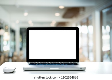 Conceptual workspace,Empty space white desk on Laptop screen and wireless mouse,Interior cafe blurred background of light bokeh.