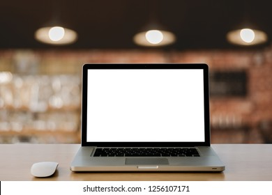 Conceptual workspace,Empty space wooden desk with Laptop blank screen and wireless mouse,cafe blurred background bokeh.