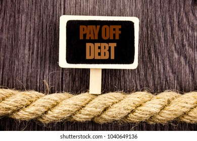 Conceptual writing text showing Pay Off Debt. Business photo showcasing Reminder To Paying Owed Financial Credit Loan Bills written Blackboard Hanging rope wooden background