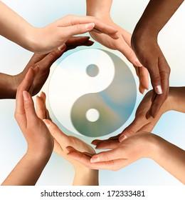 Conceptual yin-yang symbol with multiracial hands surrounding it. Balance, peace, meditation, spirituality concept.