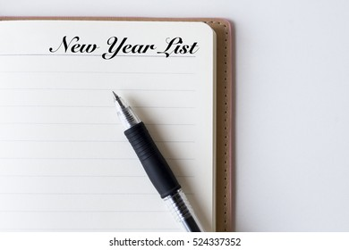 Conceptual,notebook on a white table. open diary and pen with New Year List words