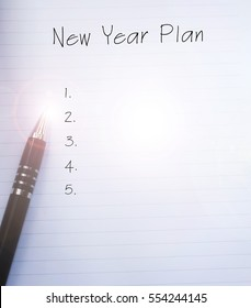 Conceptual,notebook on a white table. open diary and pen with NEW YEAR PLAN words. Copy space.