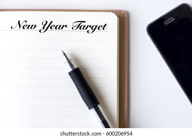 Conceptual,notebook on a white table. open diary, smartphone and pen with New Year Target words