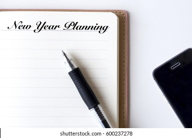 Conceptual,notebook on a white table. open diary, smartphone and pen with New Year Planning words