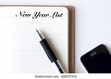 Conceptual,notebook on a white table. open diary, smartphone and pen with New Year List words