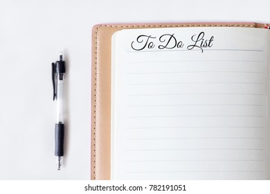 Conceptual,notebook on a white table. open diary and pen with To Do List words