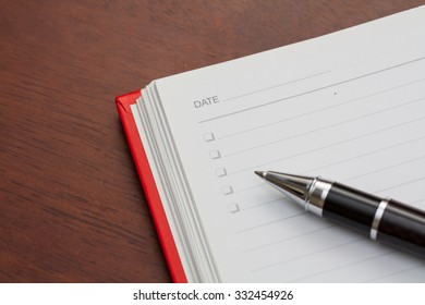 Conceptual,notebook on a wooden table. open diary and pen to record