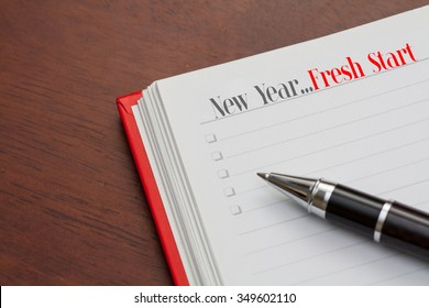 Conceptual,notebook on a wooden table. open diary and pen with new year,fresh start words