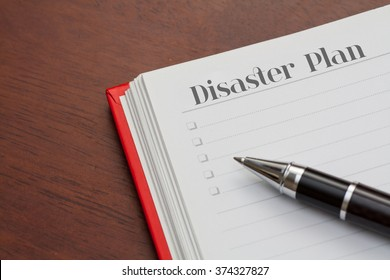 Conceptual,notebook on a wooden table. open diary and pen with disaster plan word